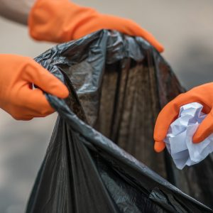 Men and women helped to collect garbage in a black bag.
